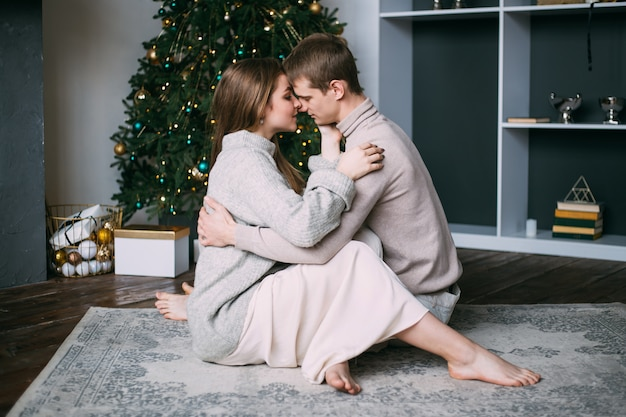 Young couple hugging at home on christmas winter holidays