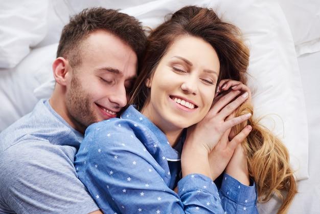 朝のベッドで抱き締める若いカップル