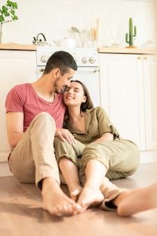 Молодая пара обнимается на кухне