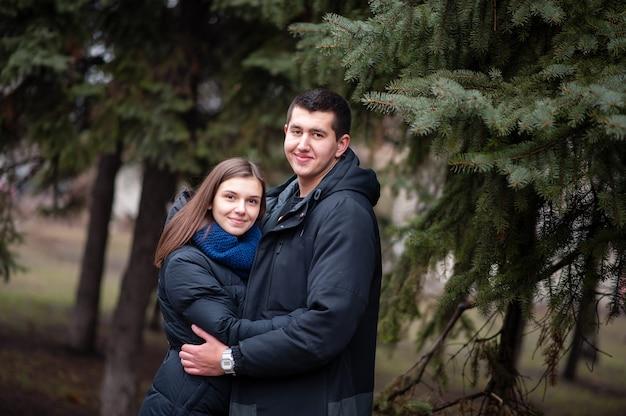 Молодая пара, обнимающаяся в парке