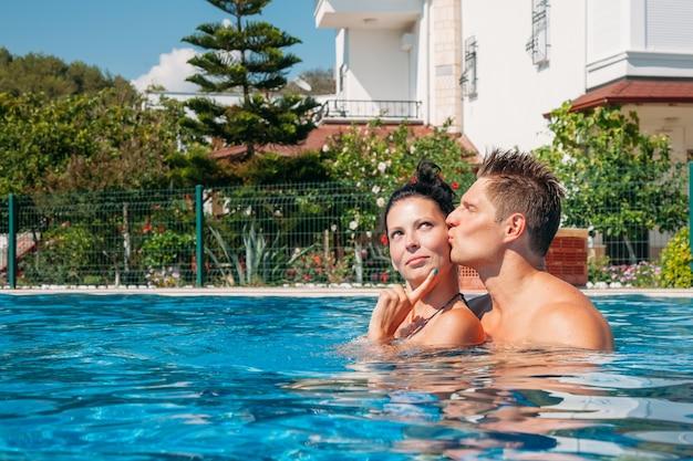 プールで抱き締める若いカップル幸せな家族アクティブレジャースイミングプールコンセプトカップル夏休み中にリラックスするのが大好き