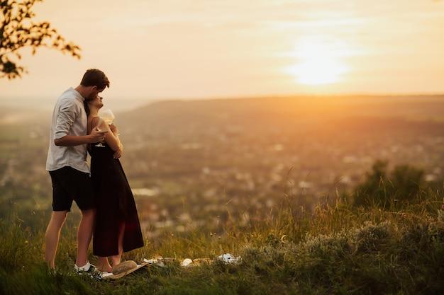 山の素晴らしいオレンジ色の夕日を抱き締める若いカップル。