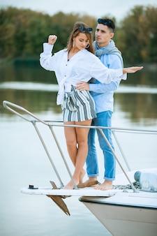 Молодая пара обниматься на палубе парусника. романтическая пара на прогулочном катере. счастливые состоятельный мужчина и женщина на частной лодке совершают морское путешествие. пара в свадебном путешествии на яхте