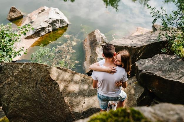 Молодая пара обнимается на камне у озера