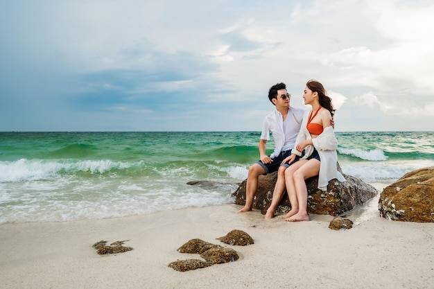 Young couple hugging on the rock of sea beach at koh munnork island, rayong, thailand