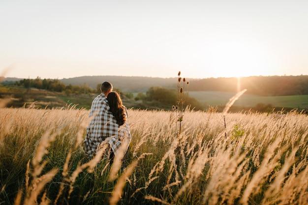 Молодая пара обниматься, стоя спиной, люди, покрытые одеялом, на закате осенью на открытом воздухе. понятие дружной семьи.