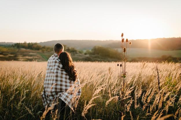 Молодая пара обнимается, стоит спиной, люди накрыты одеялом, на закате осенью на открытом воздухе