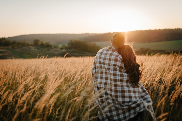 Young couple hugging, standing back, people covered with blanket, at sunset in autumn outdoor. at field grass on background of sun. full length. close up.
