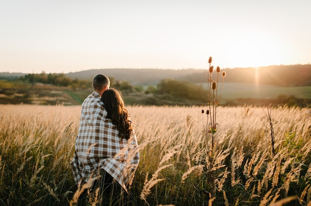 Young couple hugging, standing back, people covered with blanket, at sunset in autumn an outdoor