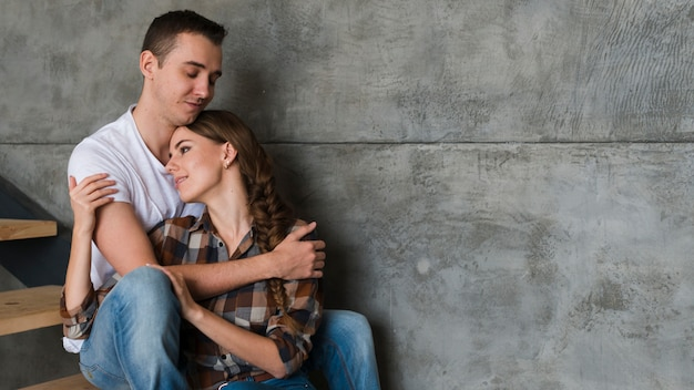 Young couple hugging on steps at home