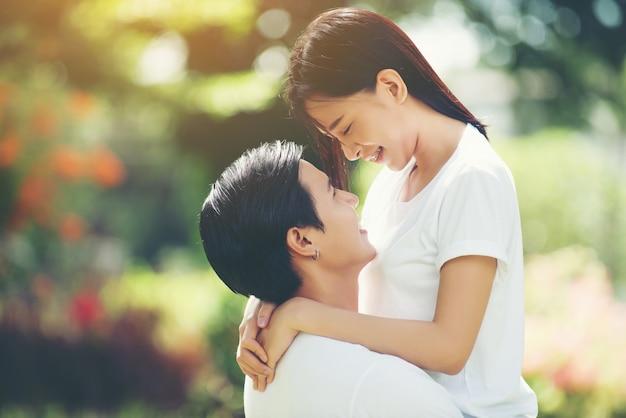 一緒にリラックスして歩くときに一緒に抱擁する若いカップル
