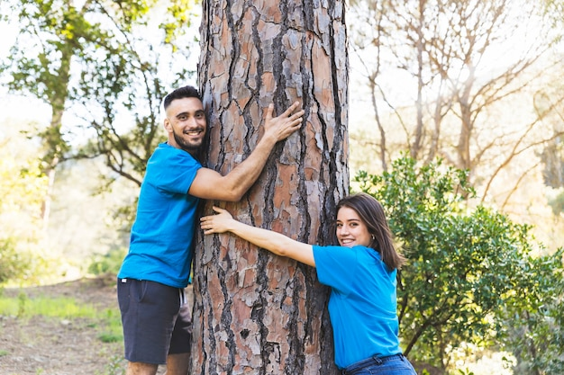 Young couple hugging tree trunk
