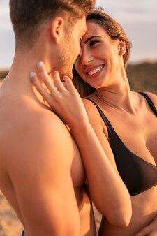 お互いを見ながら抱き締める若いカップル