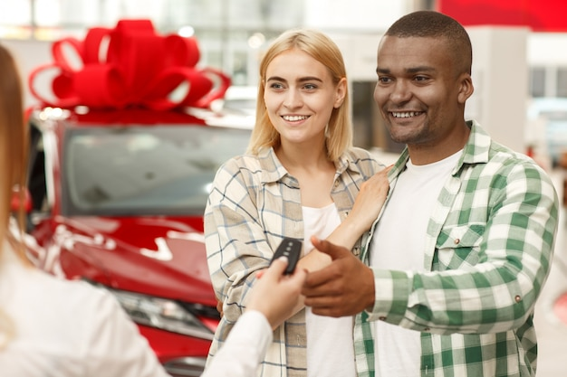 Young couple hugging while receiving keys to their new automobile from car seller.