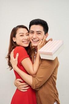 包まれたプレゼントで抱き締める若いカップル。男性を抱きしめ、リボンでプレゼントを持っている女性