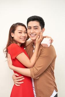 Молодая пара обниматься с обернутым настоящим. женщина обнимает мужчину и держит подарок с лентой