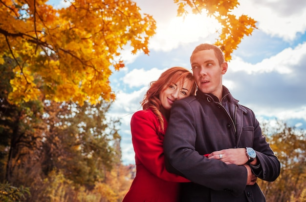 Young couple hugs in autumn forest.
