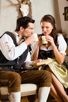 Young couple in a hunter's cabin drinking tea