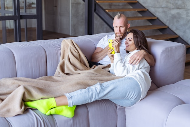 아늑한 담요 아래 소파에 있는 집에 있는 젊은 부부 남편과 아내는 전화로 셀카를 찍는다
