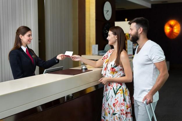 젊은 부부, 남편과 아내는 호텔에 체크인하고 여권을 제공합니다.