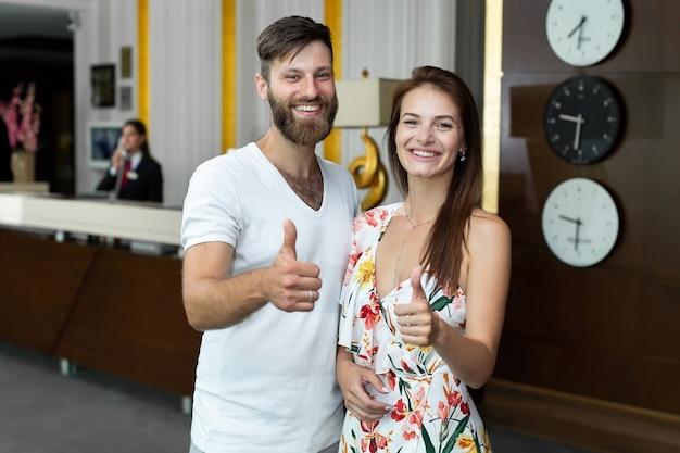 若いカップル、夫と妻は、ホテルにチェックインし、親指をあきらめます。