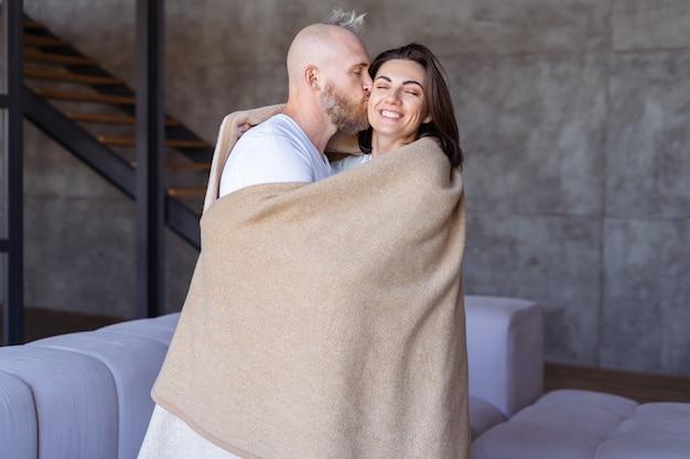 Coppia giovane marito e moglie a casa si abbracciano sotto un'accogliente coperta calda, si abbracciano, mostrano sentimenti teneri