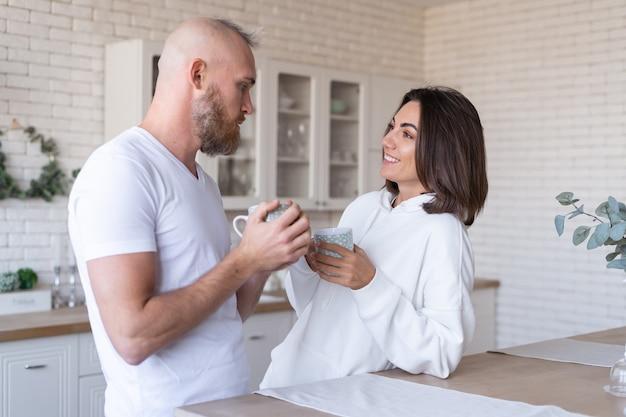 Молодая пара муж с женой дома на кухне, счастливая улыбка смеются, пьют кофе по утрам