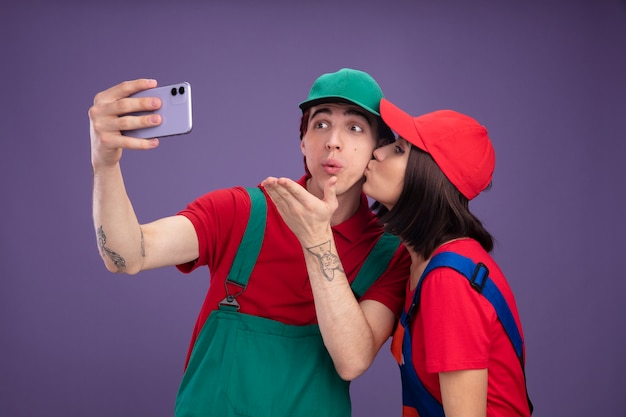 Young couple impressed guy confident girl in construction worker uniform and cap taking selfie together girl kissing guy on cheek guy sending blow kiss isolated on purple wall