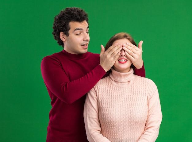 젊은 부부는 녹색 벽에 고립된 그녀를 보고 손으로 그녀의 눈을 덮고 흥분된 여자 뒤에 서 있는 감동 남자
