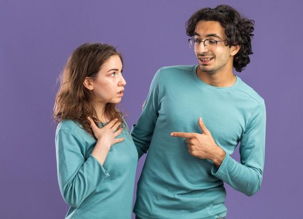 Giovane coppia impressionata donna sorridente uomo che indossa pigiama uomo con gli occhiali che punta alla donna donna che tiene la mano sul petto entrambi si guardano l'un l'altro isolato sul muro viola