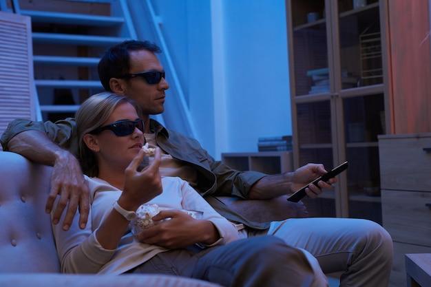 소파에 앉아 집에서 3d 영화를 보는 동안 팝콘을 먹고 3d 안경에 젊은 부부
