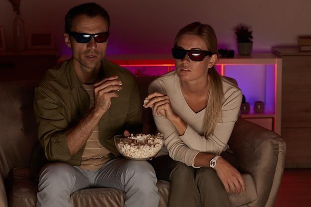 自宅の部屋でテレビを見ながらソファに座ってポップコーンを食べる3dメガネの若いカップル