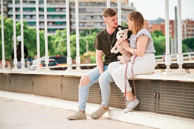 都市のシーンで彼らの犬と橋の若いカップル