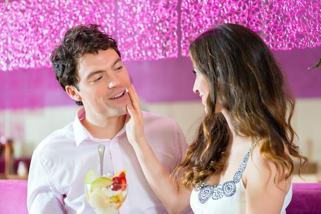 Молодая пара в кафе или кафе-мороженом, вместе едят мороженое с фруктами