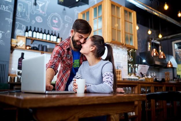 노트북 테이블에 미소와 카페 레스토랑에서 젊은 부부.