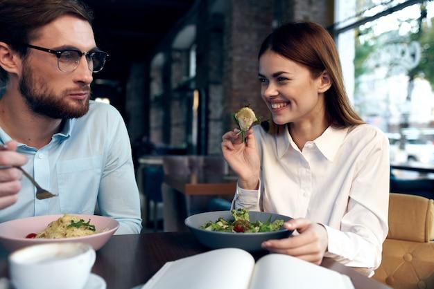 テーブルに座っているカフェで若いカップル朝食通信休憩