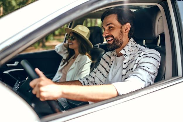 Молодая пара в новой машине. мужчина ведет машину со своей девушкой и веселится. покупка и аренда авто. путешествия, туризм, отдых.