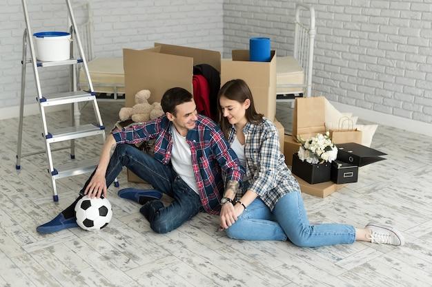 Молодая пара в новом доме отдыхает на фоне больших коробок