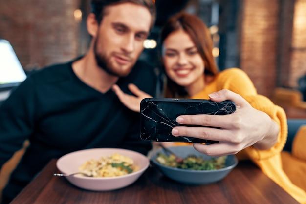 レストランの若いカップルが電話でセルフィーを作る