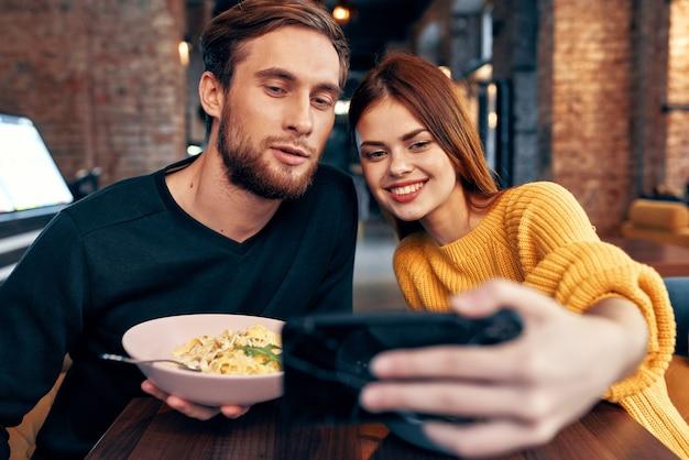 レストランの若いカップルが電話で自分撮りをします