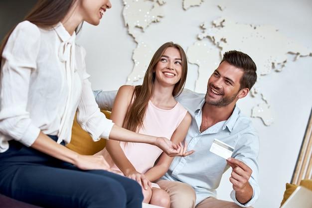 旅行代理店の若いカップルが旅行代理店にクレジットカードで支払います