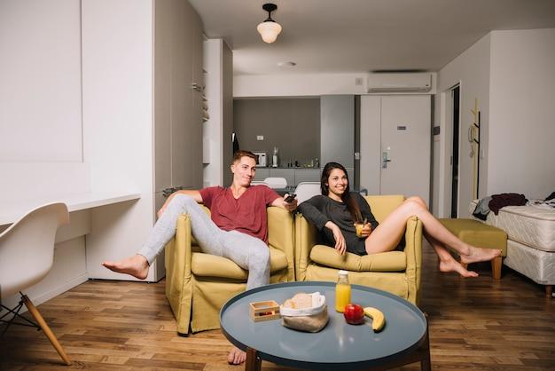 Tvを見ている肘掛け椅子の若いカップル