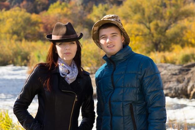 Молодая пара в осенней моде в пальто и шляпах, позирует вместе перед сельской рекой, улыбаясь в камеру