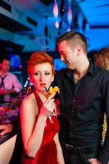 Молодая пара в баре или клубе пьет коктейли
