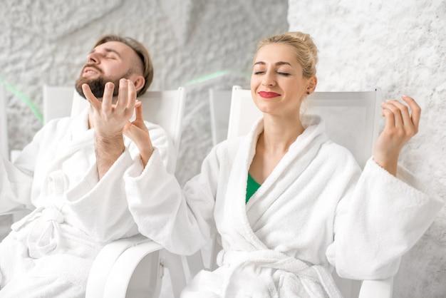 소금 방에서 명상하는 목욕 가운을 입은 젊은 부부