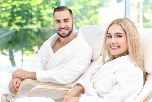 Молодая пара в халатах, расслабляясь в помещении