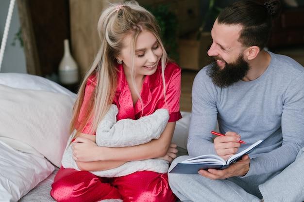 Молодая пара в постели. юбилейная планировка. улыбающийся мужчина и женщина, делая заметки.