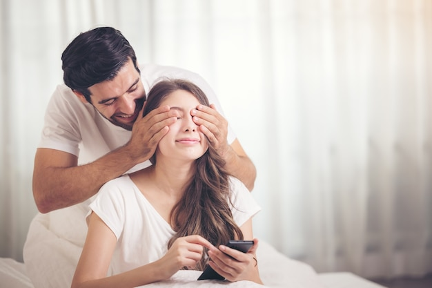 Молодая пара в постели, счастливая улыбающаяся пара, лежа покрытая одеялом и мобильным телефоном