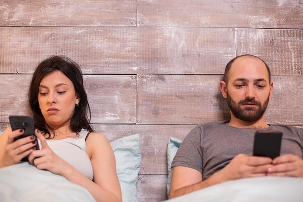 スマートフォンを使用して夜遅くにベッドで若いカップル。快適なベッド。