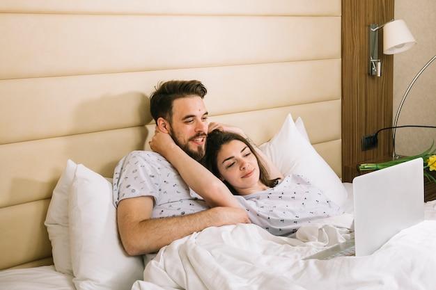 ラップトップを使用してベッドで若いカップル